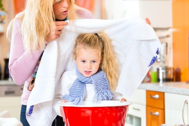 Mutterfürsorge für krankes kind mit dampfbad