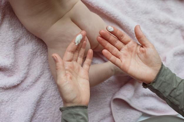 Mutterhände, die nach dem baden in den zimmerhänden einer mutter creme auf das baby auftragen, die die füße ihres babys zu hause im bett massiert