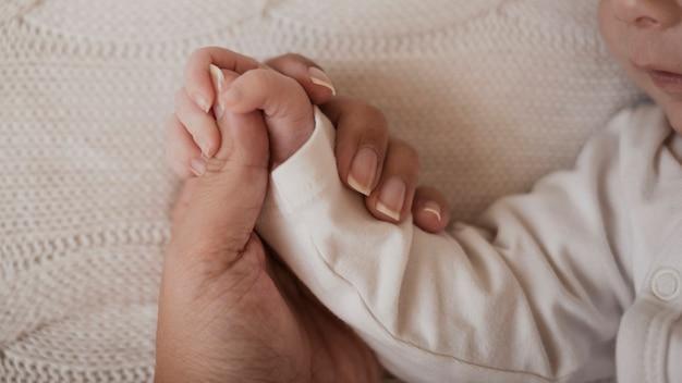 Mutterhand, die kleinen arm des babys hält