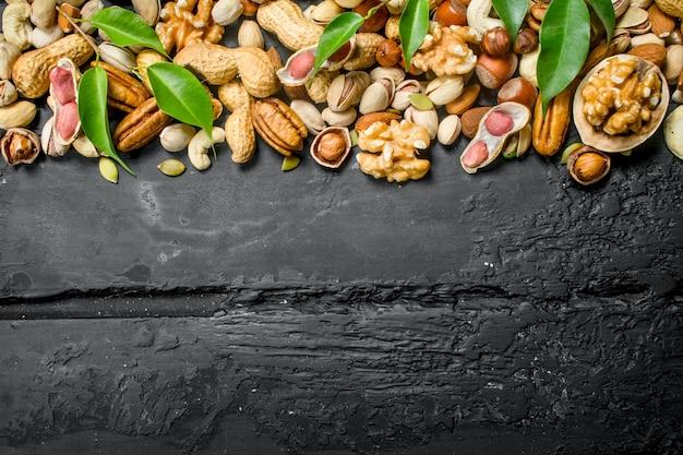 Muttern hintergrund. verschiedene arten von nüssen mit blättern. auf schwarzem rustikalem hintergrund.
