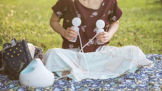 Mutterpumpenmuttermilch im park bei sonnenuntergang