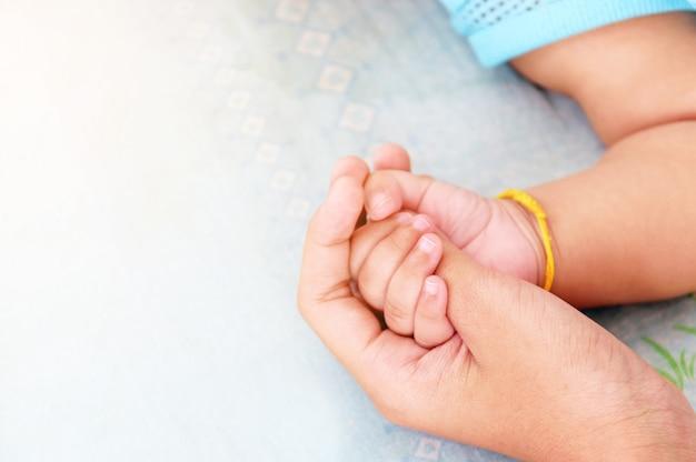 Mutters hand wiegt die hand eines babyhintergrundes für liebe und muttertag.