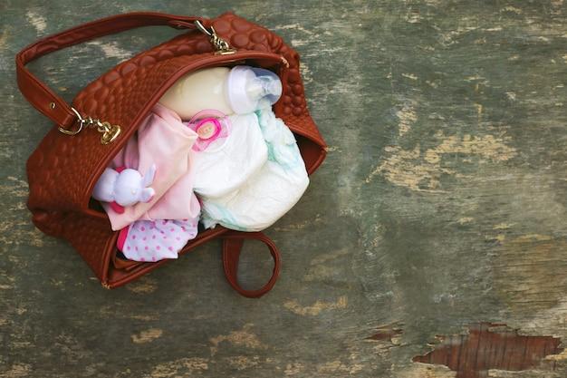 Mutters handtasche mit gegenständen zur pflege des kindes.