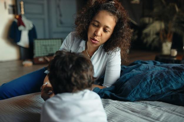 Mutterschaft, elternschaft und häuslichkeit. horizontales porträt der schönen jungen hispanischen mutter, die ihren kleinen sohn babysittet