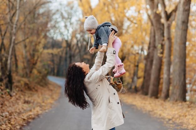 Mutterspiel der jungen frau mit kleiner tochter an der herbstparkstraße