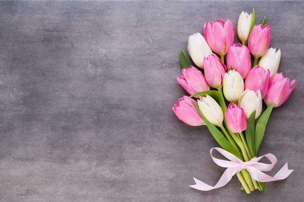 Muttertag, frauentag, ostern, rosa tulpen, geschenke auf grauem hintergrund.