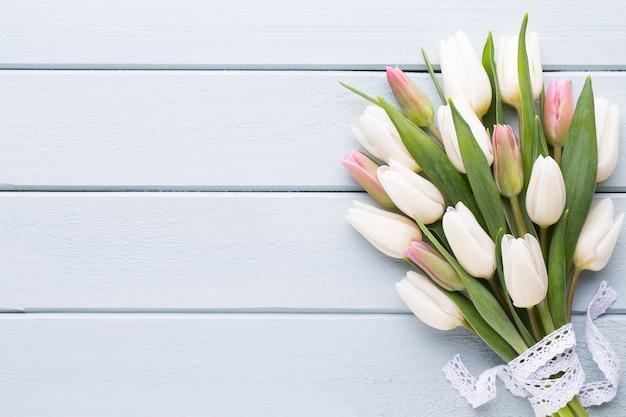 Muttertag, frauentag, ostern, weiße tulpen, geschenke auf grau.