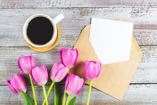 Muttertag hintergrund. frühlingsrosa tulpenblumen, tasse kaffee und leere karte auf schäbigem hölzernem hintergrund. grußkarte zum frauen- oder muttertag. flache lage, draufsicht, kopierraum.