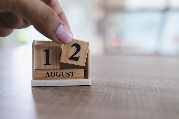 Muttertag in thailand, am 12. august, nah oben von der linken hand hebt einen hölzernen kalenderblock auf.