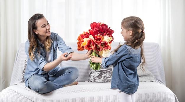 Muttertag. kleine tochter mit blumen gratuliert ihrer mutter