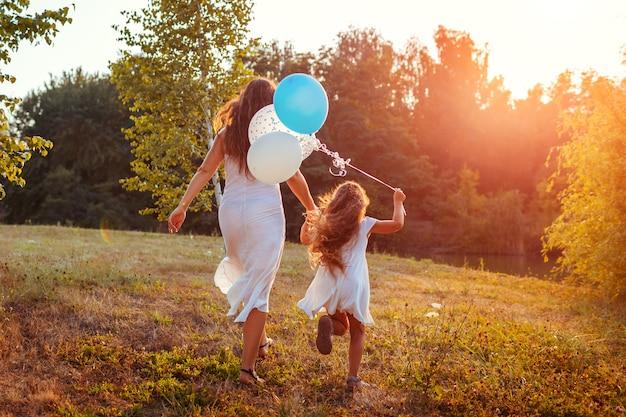 Muttertag. kleines mädchen, das mit mutter läuft und ballons in der hand hält. familie, die spaß im sommerpark hat