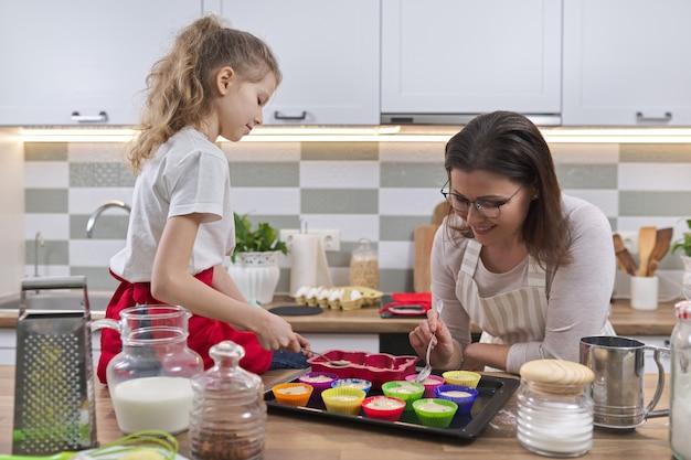 Muttertag, mutter und tochterkind bereiten cupcakes zusammen zu hause in der küche vor, frau unterrichtet kinderkochen
