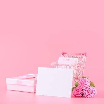 Muttertag, valentinstag-feriengeschenk-design-konzept, rosa nelkenblumenstrauß mit verpackter schachtel einzeln auf hellrosa hintergrund, kopierraum.