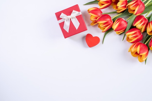 Muttertag, valentinstag hintergrund, tulpenblumenstrauß - schöner roter, gelber blumenstrauß einzeln auf weißem tisch, draufsicht, flache lage, mock-up-designkonzept.