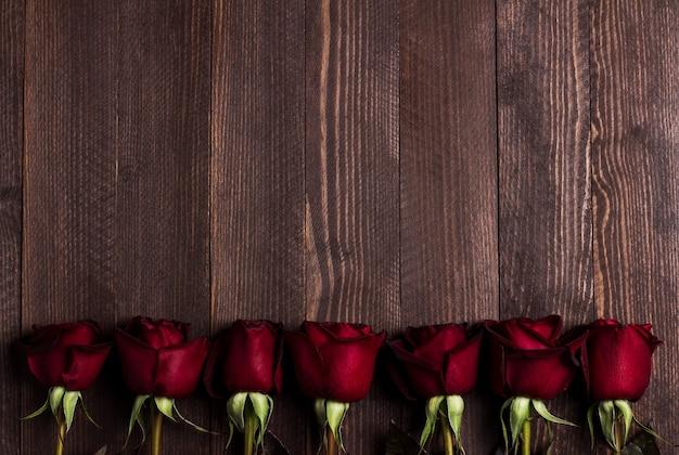 Muttertagesrot-rosengeschenküberraschung der valentinsgrußtagesfrauen auf dunklem holz