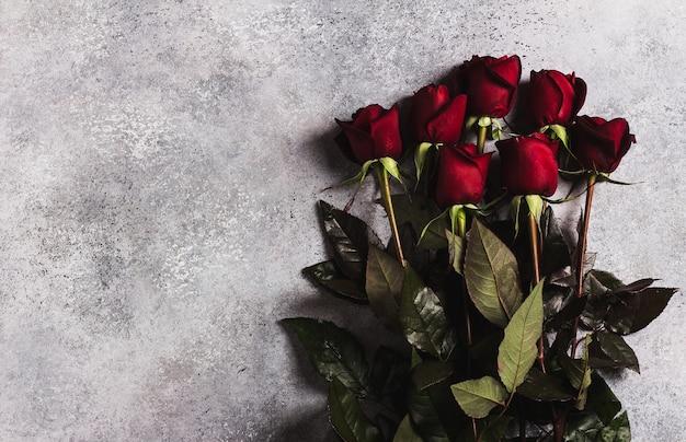 Muttertagesrot-rosengeschenküberraschung der valentinstagfrauen auf grau