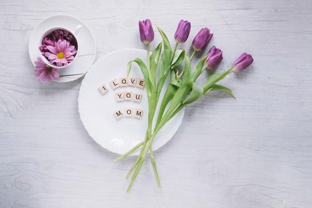 Muttertageszusammensetzung mit purpurroten rosen auf platte