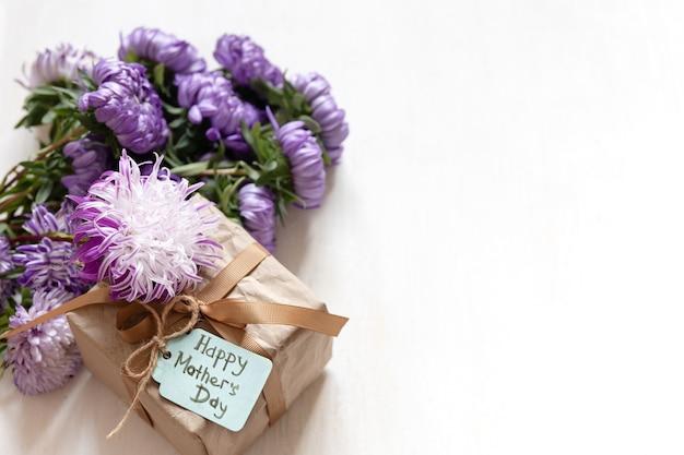 Muttertagsfestlicher hintergrund mit geschenkbox und frischen chrysanthemenblumen auf weißem hintergrund, kopienraum.