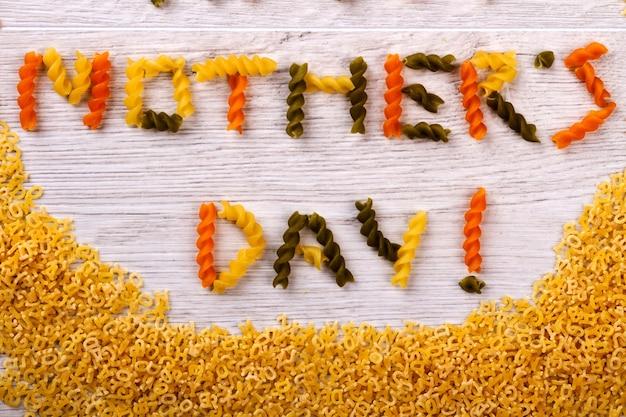 Muttertagsnudeln gebildeter text. grußworte auf holzoberfläche. schönheit der kreativität. lebensmittel als dekoratives element.