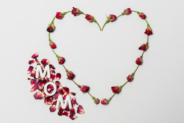 Muttertitel zwischen rotem dekorativem herzen von blumen