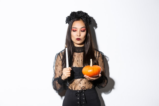 Myserious asiatische böse hexe im gotischen kleid, betrachten brennende kerze, kürbis haltend, über weißem hintergrund stehend.