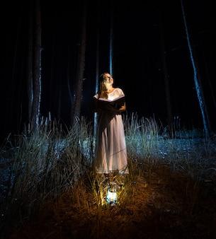 Mysteriöse aufnahme einer schönen frau im nachthemd, die ein großes magisches buch im dunklen wald liest