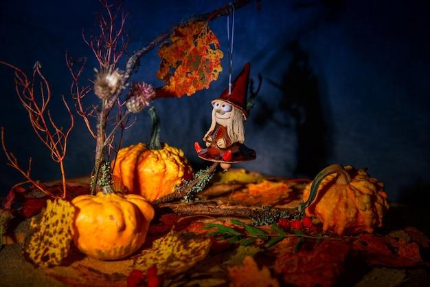 Mysteriöse gute hexe auf einem besen in einem märchennachtherbstwald mit kürbissen, halloween-hexe-spielzeugpuppenanhänger. postkarte, hintergrund, spritzer