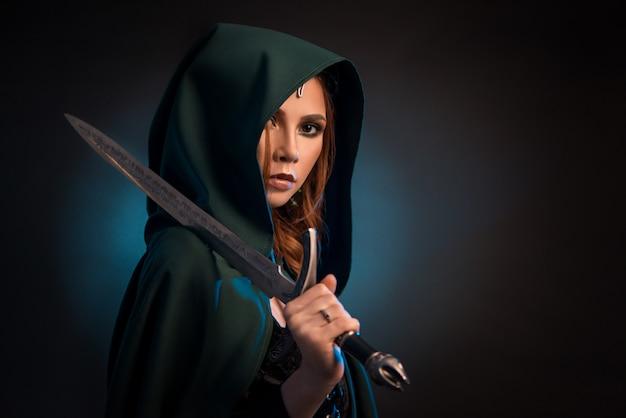Mysteriöse junge frau, die scharfes messer, grünes kap mit einer haube tragend hält.