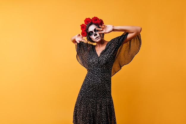 Mysteriöse lateinamerikanische frau mit ungewöhnlichem make-up für halloween. mädchen mit rosen in locken posiert und macht ihre hände ungewöhnliche bewegungen