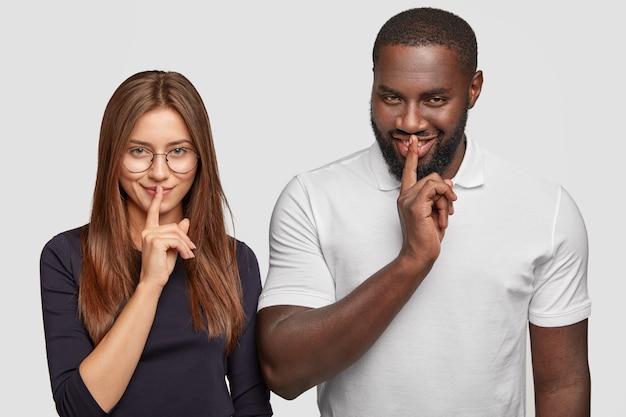Mysteriöse multiethnische frau und mann schauen heimlich aus, halten beide zeigefinger auf den lippen, während sie versuchen, stumm zu sein