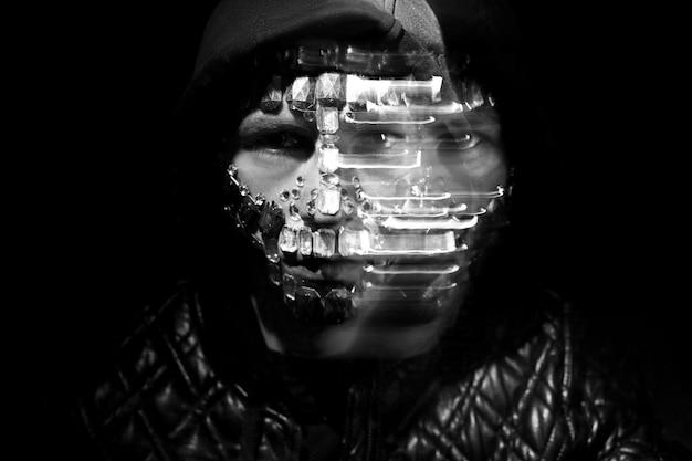 Mysteriöse mystische erscheinung eines mannes. kunstporträt eines vermummten mannes mit großen strasssteinen im gesicht. auf dem gesicht des mannes funkeln große kristalle im dunkeln. unscharf verschwommen