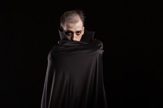 Mysteriöser mann, der sich zu halloween wie ein vampir verkleidet hat. dracula versteckt sich hinter seinem umhang. gruseliger mensch.