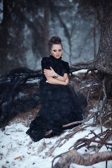 Mysteriöses kunstporträt des schönen brunette im langen schwarzen modischen kleid