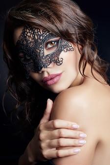 Mysteriöses mädchen in der schwarzen maske auf gesicht, maskerade