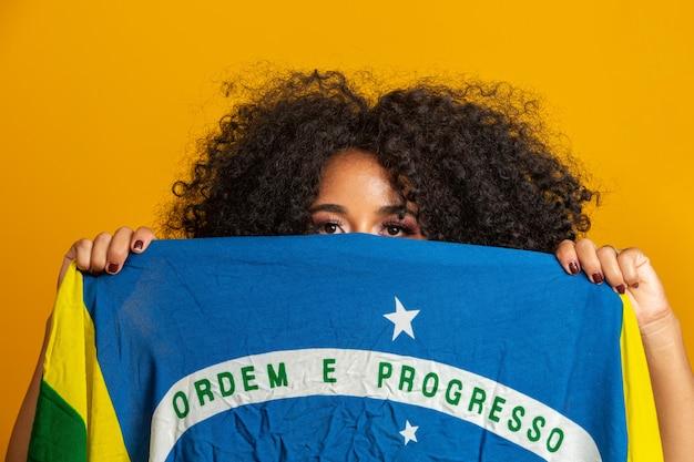 Mysteriousblack frauenfan, der eine brasilianische flagge in ihrem gesicht hält. brasilien farben in gelber wand,