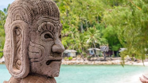 Mystic skulptur am strand von haad salat in ko phangan. hügel mit kokospalmen. thailand