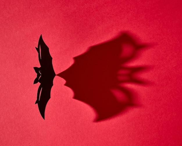 Mystische karte aus handgefertigter papierfledermaus mit einem muster aus einem schatten auf einem roten hintergrund mit kopierraum für text. halloween. flach liegen