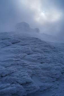 Mystische landschaft mit einem alten verlassenen observatorium auf einem berg. strenges winterwetter mit nebel, schneeverwehungen und raureif. karpaten, ukraine, pip ivan peak (schwarzer berg)