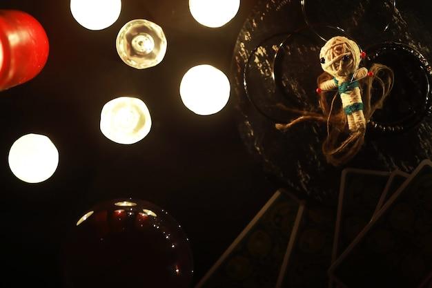 Mystisches stillleben mit voodoo-puppe die tarotkarten bücher böse kerzen und hexerei-objekte