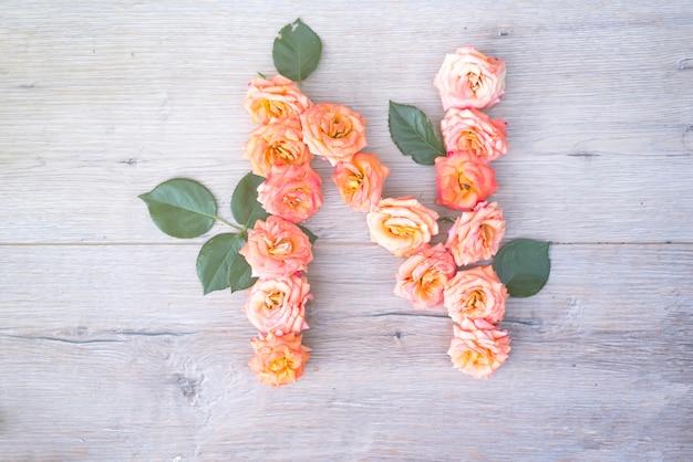 N, rosenblumenalphabet lokalisiert auf grauem hölzernem hintergrund, flache lage