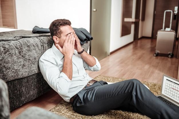 Nach dem arbeitstag. dunkelhaariger geschäftsmann, der sich nach dem arbeitstag erschöpft und extrem müde fühlt