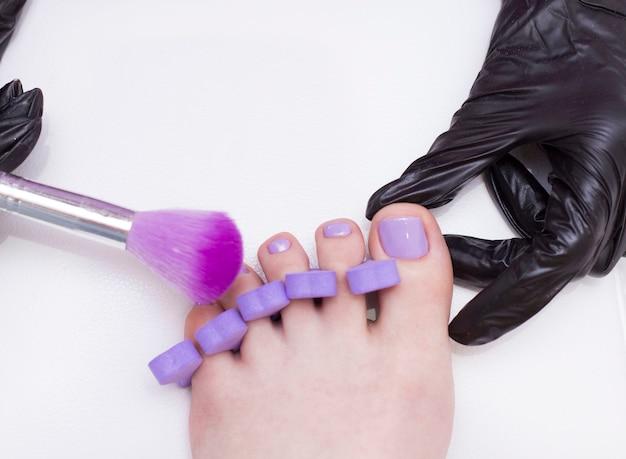 Nach dem auftragen des lila nagellacks schüttelt der pediküre-meister den staub mit einem flauschigen pinsel ab. eine bürste zum reinigen von staub von den nägeln.