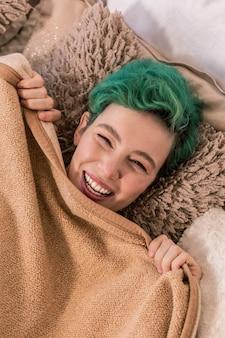 Nach dem aufwachen. grünhaarige frau, die sich nach dem aufwachen in ihrem gemütlichen schlafzimmer fröhlich und glücklich fühlt