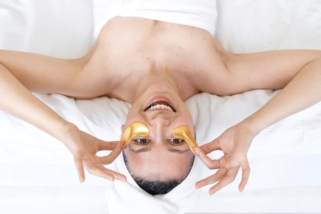 Nach dem duschen wird das mädchen in ein handtuch gewickelt und trägt kosmetische pflaster für die haut unter den augen. kosmetische eingriffe zu hause
