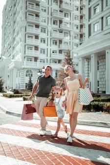 Nach dem einkaufen. glückliches paar und ihre tochter halten einkaufstüten und lachen gemeinsam über die straße.
