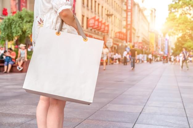 Nach dem shopping-tag. nahaufnahme einer jungen frau, die einkaufstüten trägt, während sie die straße entlang geht