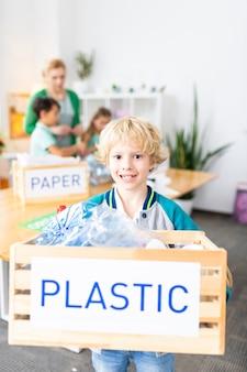 Nach dem sortieren von abfällen. hübscher lustiger schüler, der eine kiste mit plastik hält, nachdem er in der schule abfälle sortiert hat