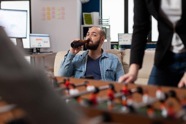 Nach der arbeit trinkt ein mann alkohol beim tischfußball, der ein spielzeugspiel beobachtet. kaukasische geschäftsleute spielen im büro, um eine flasche bier zu halten und spaß zu haben