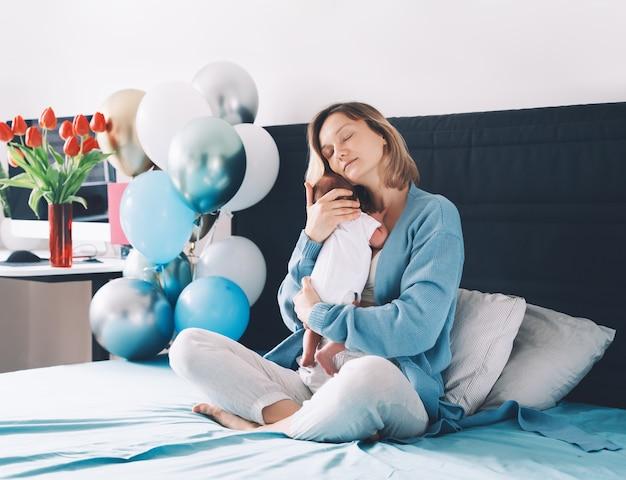 Nach der babygeburt hält mutter und baby zu hause ihr neugeborenes in händen