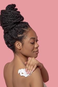 Nach der massage. dunkelhäutige frau, die sich nach der massage mit einer serviette den körper abwischt